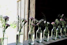 Så vackert med manga glasvaser/flaskor med enkla blommor i på vårt lantbröllop