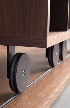 Interior Design Details - Industrial Close Ups | The wheels on the bottoms of this sliding bookcase add an industrial touch to the modern piece of furniture.