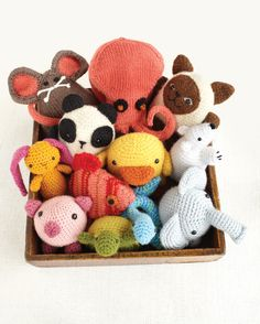 A menagerie of knitted and crocheted creatures peeks out of a box; they are called amigurumi, after the Japanese art of crocheting small animals.