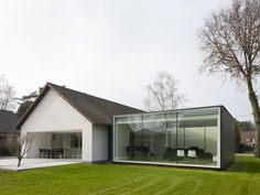 an intervention of an existing farmhouse in genk, belgium, the 'framework house' is a single family dwelling by   belgian firm cocoon architecten. dating from the 70s, the structure was modified, extending the interior space beyond the building's footprint & closer towards the garden, creating a new relationship with the outdoors.