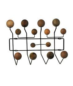 Design Charles e Ray Eames, 1963. Cabideiro de parede com estrutura de metal pintado em preto e apoio em esferas de diversos tipos de madeira macica.
