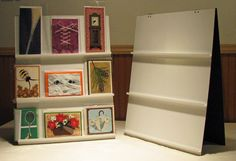 Tabletop Card Display - Cheap and Easy made from thin, coated, scrap particle board and flashing, The flashing is glued, and the hinges are put on with white craft brads
