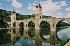 Discover Pont Valentre in Cahors, France: A century bridge built as a fortress, where the devil lurks on one of its towers. Cades Cove, Pigeon Forge, Lonely Planet, Wyoming, Tennessee, Old Bridges, Bridge Construction, Alpine Village, Architecture