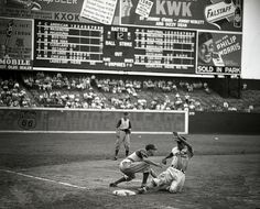 Musial at Sportsman's Park in St. Louis as he slides safely into third base.