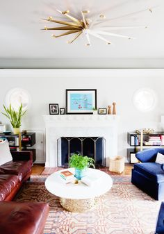 An elegant and colorful living room space with leaning art on fireplace mantle, blue chairs, and gold light fixture