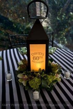 Cool lantern 60th birthday centerpiece.  I like the lanterns with pictures and the striped table clothes.