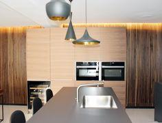La pared de madera de nogal aporta mucha personalidad a esta cocina. La luz indirecta sobre ella crea un ambiente mucho más cálido.  El contraste del blanco y el negro se suaviza sobre este fondo natural de madera.