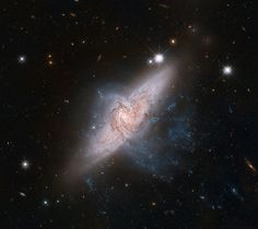 NASA's Hubble Space Telescope shows a rare view of a pair of overlapping galaxies, called NGC 3314. The two galaxies look as if they are colliding, but they are actually separated by tens of millions of light-years, or about ten times the distance between our Milky Way and the neighboring Andromeda galaxy. The chance alignment of the two galaxies, as seen from Earth, gives a unique look at the silhouetted spiral arms in the closer face-on spiral, NGC 3314A.