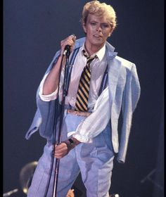 David Bowie performs in a blue suit and stripy tie