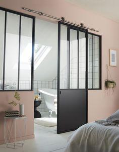 Mur rose, verrière noire, salle de bains blanche