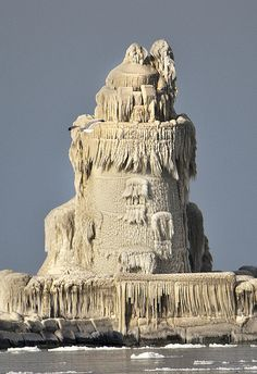 Extremely cold temperatures caused the crashing waves from Lake Erie to freeze on the surface of the Cleveland Harbor West Pierhead Lighthouse forming a bizzarre structure - much like a sand castle - Ohio - USA