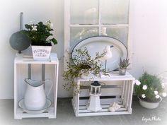 Alte Weinkisten, altes Fenster und Emaille kombiniert mit weißen und grünen Pflanzen