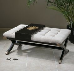 Uttermost Gizela Ottoman. Rubbed black, solid wood frame structure with brass feet and a sliding tray atop the button-tufted, off-white cushioned top. Fabric is stain resistant polyester.