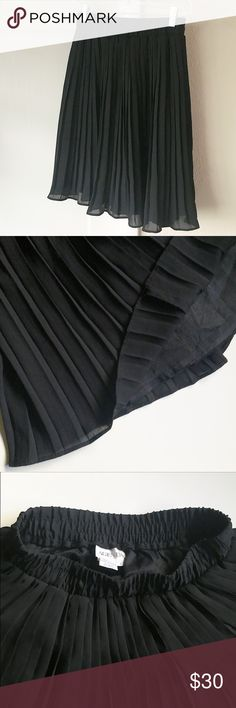 """Black Pleated Skirt Black pleated skirt. Lined. Elastic waist about 1.5"""" wide. Skirt about 22"""" long from top of waist band to hem. When laid flat, waist is about 13"""" wide - and is very stretchy. Shell is 100% Polyester. Lining is 100% Acetate. Size 6 - would fit a small or medium. For reference, I'm 5'2 and this hit right below my knee (when waistband just under my navel). Please note this is not asymmetrical - weird angle in first photo. Fit is more A-line. Worn gently a few times. In great…"""