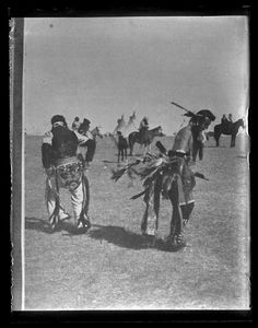 Glass negative (black and white); two Sioux men in dance regalia performing a dance outdoors; people mounted on horses and tipis in the background; USA.  Photographic process