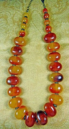 SoVintageous is offering this fabulous vintage necklace of marbled caramel amber Bakelite beads, separated by ornate gun-  metal spacers and chain.  A beautiful stylish design, the necklace tests posi