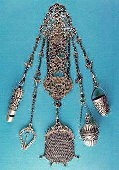 Sterling silver chatelaine complete with a whistle, folding buttonhook, coin purse, vinaigrette, and thimble bucket