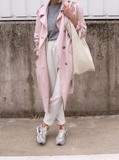 Acheter la tenue sur Lookastic: https://lookastic.fr/mode-femme/tenues/trench-t-shirt-a-col-rond-pantalon-carotte/13641 — T-shirt à col rond gris — Trench rose — Sac fourre-tout en toile beige — Pantalon carotte blanc — Chaussures de sport grises