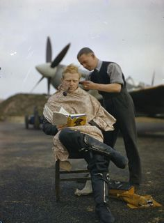 A pilot at Fairlop airfield in Essex has a haircut during a break between sweeps. A Supermarine Spitfire is in the background. November 1942: (IWM)