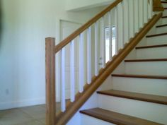 Simple white, squared spindles. Wooden staircase with white risers. Wooden banister.