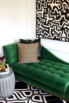 Green velvet daybed in living space with black and white art and rug