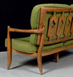 Robert GUILLERME et Jacques CHAMBRON Canapé en bois naturel à dossier ajouré à décor géométrique, garniture de tissu vert Hauteur: 83 cm, Largeur: 148 cm, Profondeur: 69 cm (État d'usage)