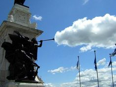 A statue of an angel summons a rain cloud. | 30 Incredible Once In A LifetimeShots