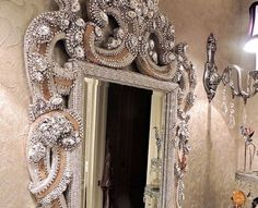 Elaborate mirror with candle holder made with vintage jewelry and Swarovski crystals. This one-of-a-kind piece is completely adorned with blinged out by Douglas Cloutier.