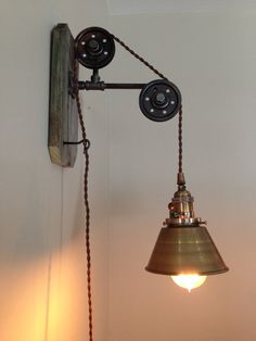 This light is an industrial style light made from reclaimed wood with black iron pipe and aged steel pulleys. This listing is for one light;