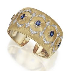 18 KARAT TWO-COLOR GOLD, SAPPHIRE AND DIAMOND CUFF BRACELET, BUCCELLATI, ITALY The hinged textured gold cuff set with oval sapphires, accented by round diamonds weighing approximately 1.00 carat, mounted in yellow and white gold, internal circumference 6½ inches, signed M. Buccellati.  With signed box.