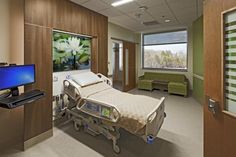 Patient rooms are same-handed and have lighted handrails from the head of the bed to the outboard toilet/shower, which has a translucent window. All rooms are configured for patient lifts, but only the ADA/bariatric rooms have them installed. Large nature images in each room support a design intent to provide access to nature. Kieran Reynolds Photography.