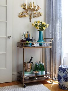 Brass bar cart styling with blue and white garden stool and light blue curtains