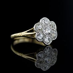 Seven old mine cut diamonds are set together in a traditional cluster setting in this antique style diamond ring. The low profile floral motif cluster is embraced by a tri-furcated shank in 18 karat gold. Mid-century English hallmarks.