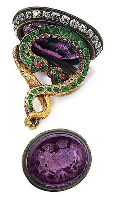 A late 19th century amethyst and emerald fob. Designed as intertwining two snakes, set with emeralds, holding an intaglio of oval amethyst, engraved with coat of arms, set in a diamond framed case, mounted in gold and silver.