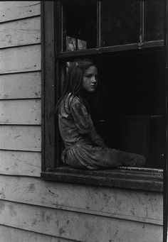 Young girl looking out of her window, during the Great Depression