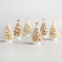 Create a festive holiday display with our retro bottlebrush trees, covered with chunky glitter and sitting on circular wood bases. Each set - one in copper and bronze hues, the other in champagne and silver - is studded with antiqued ball ornaments for plenty of yuletide sparkle.