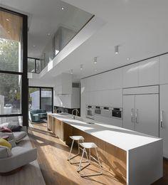 Cucina a vista bianca abbinata a zona relax con isola molto grande in legno