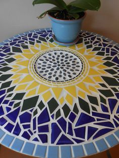 Bright and Cheerful SunFlower Mosaic Table. Round heavy table with a thick solid wood top and heavy round/ tubular brushed chrome steel legs. This is one of the funnest mosaic designs I do. I love how organic it is with the mostly broken tiles and natural pebbles. The colors are very bright and definitely eye catching. The center of this sunflower is made with natural dark colored pebbles that are mostly oval shaped which are surrounded by rings (one of each) black, chartreuse and yellow…