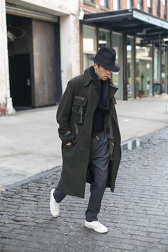 Green mens oversized overcoat by Yohji Yamamoto in a slouchy yet refined menswear, topped with a fedora by J. Lindeberg