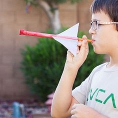 A DIY paper rocket that you launch with a straw! Perfect for antsy kids stuck inside because of the weather