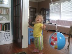 Batting at a beach ball on a string hung from the ceiling