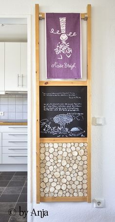 An Ikea Ivar side unit is used to make a wall decoration. Two pieces of particle board are incorporated: one painted with blackboard paint; and the other decorated with slices of tree branches.