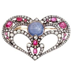 An antique silver, gold, diamond and gem set brooch, 19th century. The heart-shaped openwork brooch set to the centre with a cabochon star sapphire, surrounded by diamonds highlighted with spinels, mounted in silver and gold. #antique #brooch
