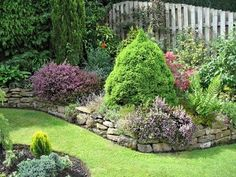 Low stone walls bring flower beds  closer for viewing, but keep garden in proportion with landscape