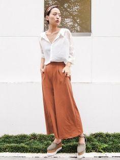 ブラウンレッドのワイドパンツには、鎖骨が見えるように胸元を開けたシャツがよく似合います。ターバンや足先まで計算された初秋のコーディネートです。