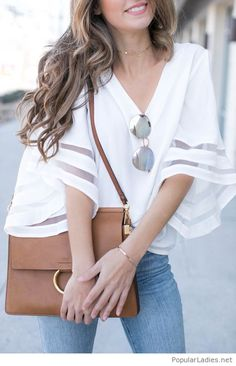 White top, jeans and a brown bag