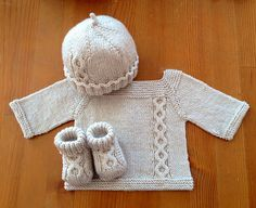 Jeudi - Top-down knitted baby sweater with raglan sleeves, back buttoning and a lovely off-center cable replicated on matching booties and hat.