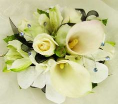 Popular mini calla lilies, spray roses and alstromeria lilies create a unique design wrist corsage