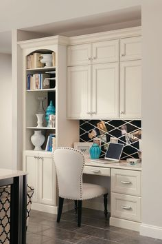 A built-in desk with bookcase and cabinets creates a seamless home office in a kitchen corner.