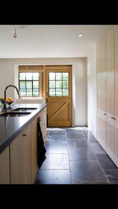 Keuken zwart werkblad en dito vloer en houten kastjes